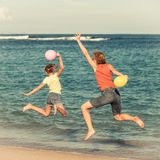 Happy  family  with balloons  jumping on the beach Stock Image