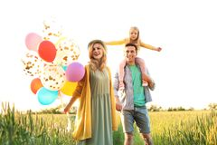 Happy family with balloons outdoors on sunny day. Happy family with colorful balloons outdoors on sunny day Royalty Free Stock Photography