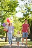 Happy family with balloons outdoors on sunny day. Happy family with colorful balloons outdoors on sunny day Stock Photos