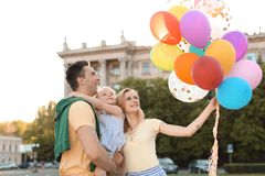 Happy family with balloons outdoors on sunny day. Happy family with colorful balloons outdoors on sunny day Stock Photography