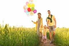 Happy family with balloons outdoors on sunny day. Happy family with colorful balloons outdoors on sunny day Royalty Free Stock Photos