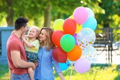 Happy family with balloons in park on sunny day. Happy family with colorful balloons in park on sunny day Stock Image