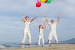 Happy family with balloons playing on the beach at the day time. Royalty Free Stock Image