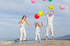 Happy family with balloons playing on the beach at the day time. Stock Image