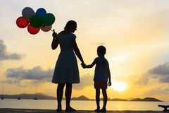 Happy family with balloons at sunset Royalty Free Stock Images