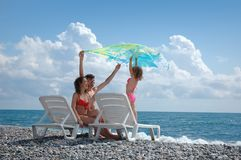 Happy family on the beach. With flying pareu Royalty Free Stock Photos