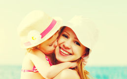 Happy family on beach. baby daughter kissing mother Royalty Free Stock Photos