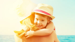 Happy family on the beach. baby girl hugging her mother Stock Images
