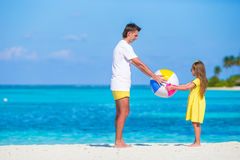 Happy family on the beach with ball having fun together Stock Photo