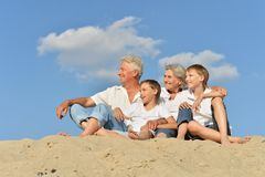 Happy family on beach. Cheerful boys with their grandparents sitting on the sand in the summer Stock Photos