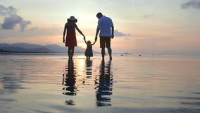 Happy family on the beach holding hands.