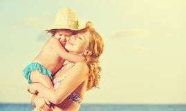 Happy family on the beach. mother and baby daughter hug. At sea royalty free stock photography
