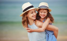 Happy family at beach. mother and child daughter hug at sea royalty free stock image