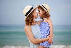 Happy family at beach. mother and child daughter hug at sea. Happy family at the beach. Mother and child daughter hug at sea stock photos