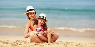 Happy family at beach. mother and child daughter hug at sea. Happy family at the beach. Mother and child daughter hug at sea stock image