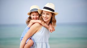 Happy family at beach. mother and child daughter hug at sea. Happy family at the beach. Mother and child daughter hug at sea royalty free stock image