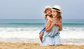 Happy family at beach. mother and child daughter hug at sea. Happy family at the beach. Mother and child daughter hug at sea stock images