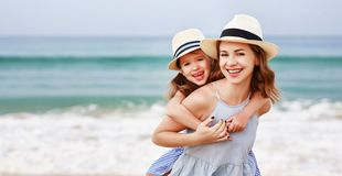 Happy family at beach. mother and child daughter hug at sunset stock photos