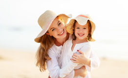 Happy family at beach. mother and child daughter hug at sunset Royalty Free Stock Photos