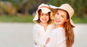 Happy family at beach. mother and child daughter hug at sunset Stock Photography