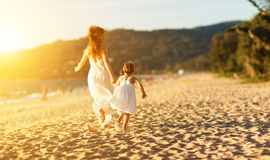 Happy family at beach. mother and child daughter run, laugh and Royalty Free Stock Image