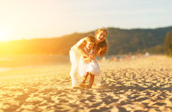 Happy family at beach. mother and child daughter run, laugh and Stock Photos