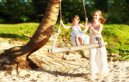 Happy family at beach. mother shook child on swing in summer. And laughs royalty free stock photography