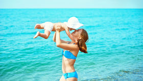 Happy family on the beach. mother throw up baby daughter  and pl Royalty Free Stock Photos
