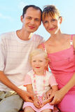 Happy family on beach, Parents hold girl for hands Stock Image