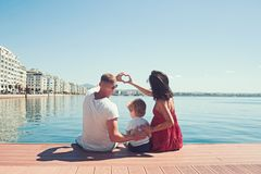 Happy family on the beach. People having fun on summer vacation. Father mother and child against blue sea and sky stock photo