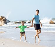 Happy family on beach playing, father with son walking sea coast Stock Image