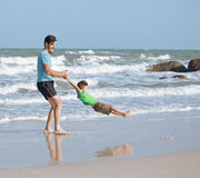 Happy family on beach playing, father with son Stock Image
