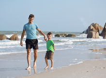 Happy family on beach playing, father with son walking sea coast, rocks behind smiling enjoy summer Stock Photo