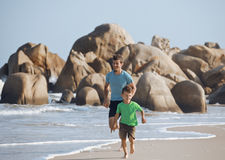 Happy family on beach playing, father with son walking sea coast, rocks behind smiling enjoy summer. Vacations, lifestyle people concept Stock Image