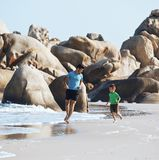 Happy family on beach playing, father with son walking sea coast, rocks behind smiling enjoy summer. Vietnam Stock Images