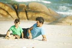 Happy family on beach playing, father with son walking sea coast, rocks behind smiling taking vacation royalty free stock photos