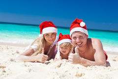 Happy family on beach in Santa hats, celebration christmas Stock Images