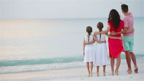 Happy beautiful family on the beach. Back view of parents and kids at sunset stock footage