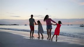 Happy beautiful family on a beach during summer vacation. Family of four have fun at sunset on the beach. Happy family on a beach during summer vacation stock video footage