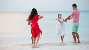 Happy beautiful family on a beach during summer vacation. Family of four have fun at sunset on the beach stock video