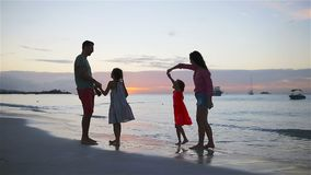 Parents and two kids have a lot of fun on the beach at sunset. Family of four in love, happy and beautiful. Happy family on a beach during summer vacation stock video footage