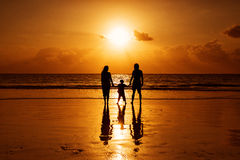 Happy family on a beach at sunrise with child mother and father Royalty Free Stock Photography