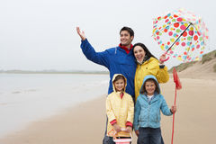 Happy family on beach with umbrella Stock Photo
