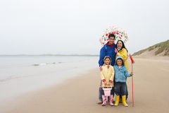Happy family on beach with umbrella Royalty Free Stock Photo