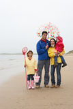 Happy family on beach with umbrella Royalty Free Stock Photos