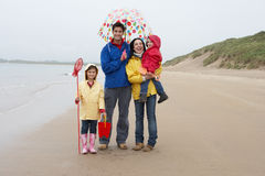 Happy family on beach with umbrella Stock Images