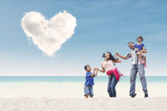 Happy family at beach under heart cloud Stock Image