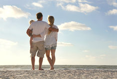 Happy Family On Beach Vacation Looking at Ocean. The backs of a happy family of three people, including mother, father and baby are standing on a white sand royalty free stock image