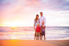 Happy Family on the Beach. Happy Young Family of Four on the Beach at Sunset Royalty Free Stock Images
