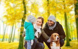Happy family with beagle dog in autumn park stock photography